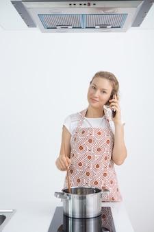Moderna dona de casa cozinhando e falando no telefone