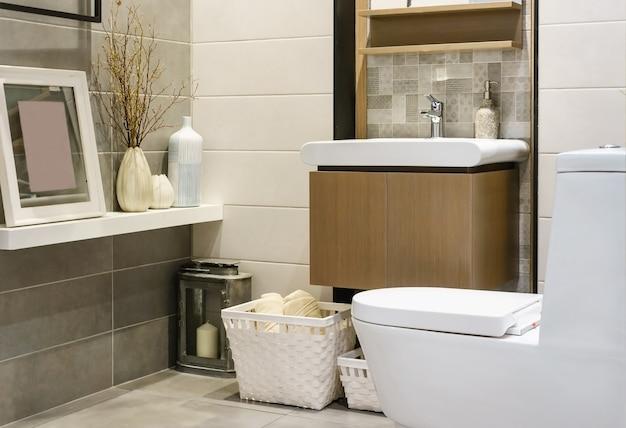 Moderna espaçosa casa de banho com azulejos brilhantes com vaso sanitário e pia. vista lateral