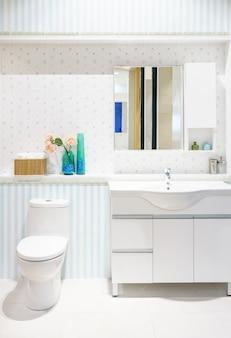 Moderna espaçosa casa de banho com azulejos brilhantes com vaso sanitário e pia