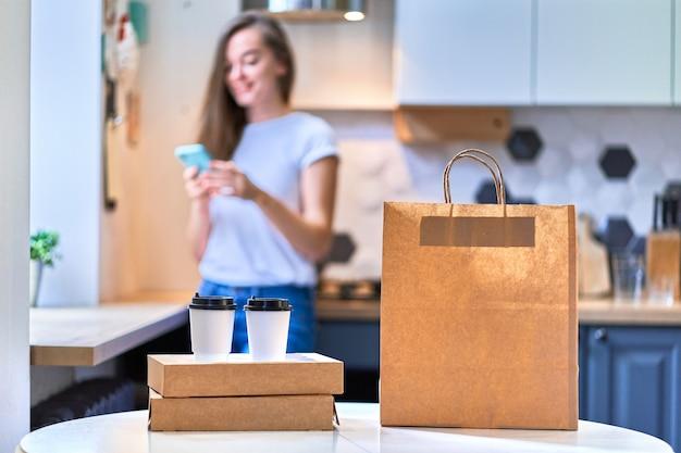Moderna ocupada fofa sorridente alegre feliz casual mulher milenar recebeu sacos de papelão e copos de papel com comida e bebidas para viagem. conceito de entrega rápida em domicílio
