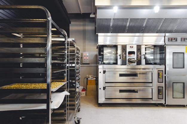 Moderna pastelaria cozinha decorada em preto, branco e aço com máquina de assar,