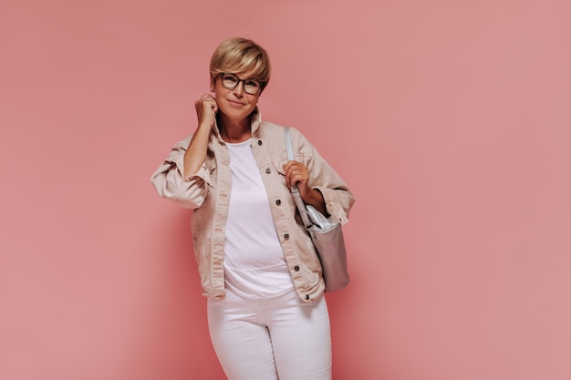 Moderna velha senhora com cabelo curto em uma jaqueta legal, calça branca e camiseta, posando com óculos e bolsa em fundo isolado.