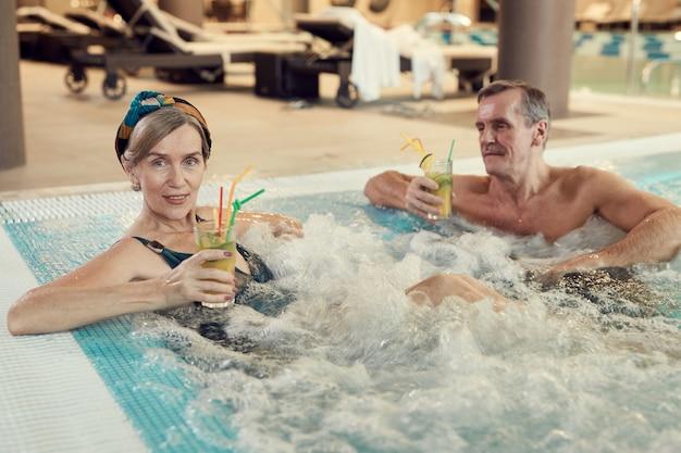 Moderno casal sênior desfrutando de banheira de hidromassagem no resort