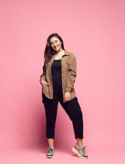 Moderno, com estilo. jovem mulher com roupa casual em fundo rosa. caráter corpopositivo, feminismo, amar a si mesma, conceito de beleza. mulher de negócios plus size, linda garota. inclusão, diversidade.