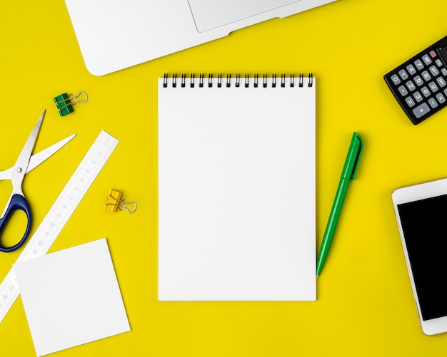 Moderno criativo brilhante amarelo escritório mesa laptop, smartphone e outros acessórios