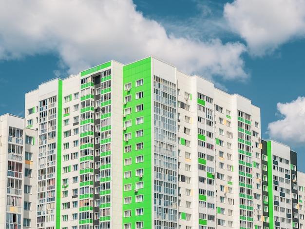 Moderno e bonito edifício residencial novo. parede colorida no fundo do céu azul. copie o espaço.