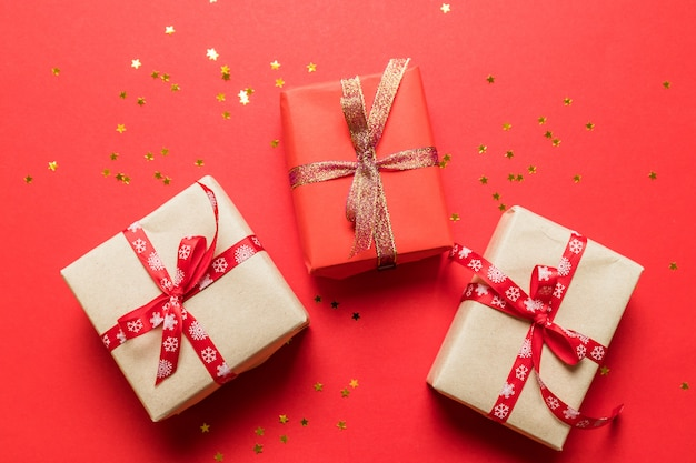 Moderno em caixas de surpresa de papel multicolor artesanato com fitas de laço brilhante ouro sobre fundo vermelho. pode usar para banner de aniversário, foto de artigo, cartaz de aniversário ou cartão postal.