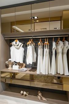 Moderno guarda-roupa de madeira com roupas penduradas no trilho no interior do closet