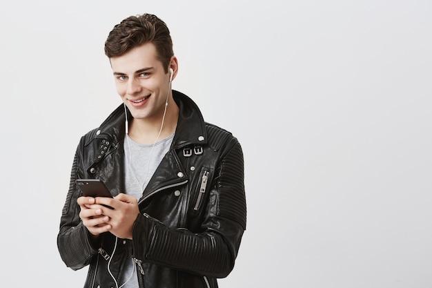 Moderno homem caucasiano jovem com cabelos escuros na jaqueta de couro preta de mensagens através de redes sociais, usando a internet 3g no dispositivo eletrônico, olhando com seus olhos azuis e sorriso atraente.