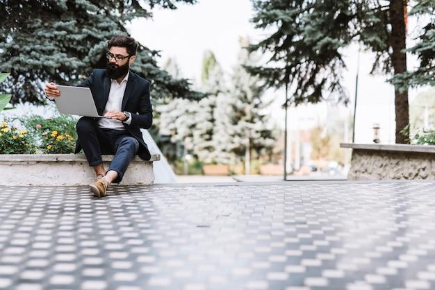 Moderno jovem empresário sentado no parque olhando para laptop