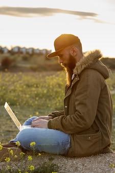 Moderno jovem sentado no campo, trabalhando ao pôr do sol com seu latop