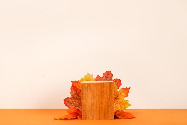 Moderno pódio de madeira de outono com decoração de folhas caindo no fundo branco