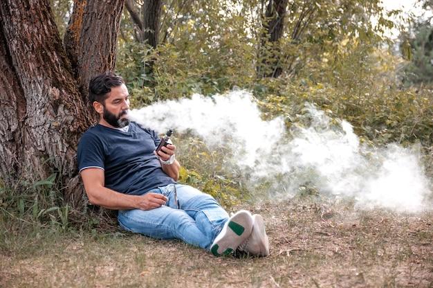 Modernvaper soprando muita fumaça usando o cigarro eletrônico vape. o homem realmente gosta do processo de fumar.