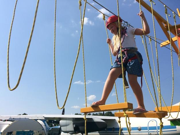 Modo de vida ativo - uma menina está passando por uma corda em uma cidade