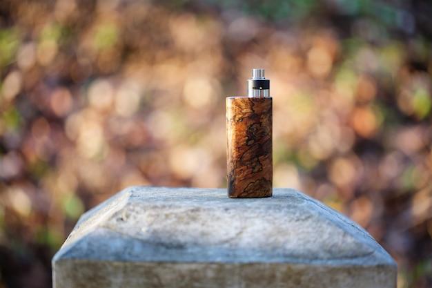 Mods de caixa de madeira estabilizada natural com atomizador de gotejamento rebuildable em bokeh textura de fundo