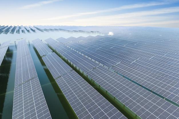 Módulos fotovoltaicos no fundo do pôr do sol e céu nublado