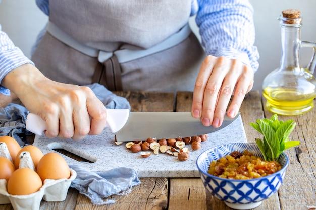 Moe avelãs. um cozinheiro mói uma noz em uma placa com uma faca.