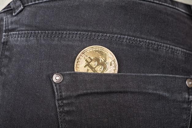 Moeda bitcoin de metal no bolso de trás do close-up de jeans, criptomoeda.