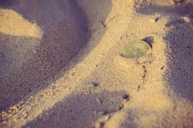 Moeda bitcoin enterrada na areia na praia