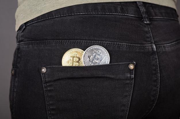 Moeda bitcoin no bolso da calça, acúmulo de criptomoeda close-up
