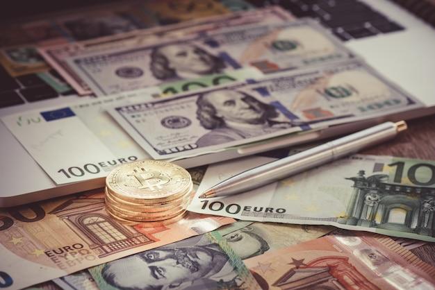 Moeda com notas de euro e dólar no teclado para negócios on-line