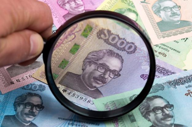 Moeda de bangladesh em uma lupa um fundo de negócios