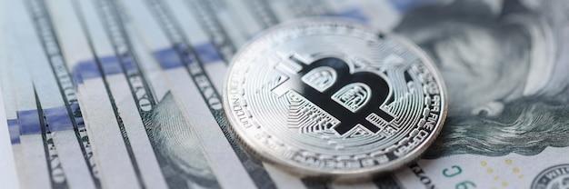 Moeda de bitcoin de prata deitada na pilha de notas de dólar, close-up, ganhando o conceito de criptomoeda