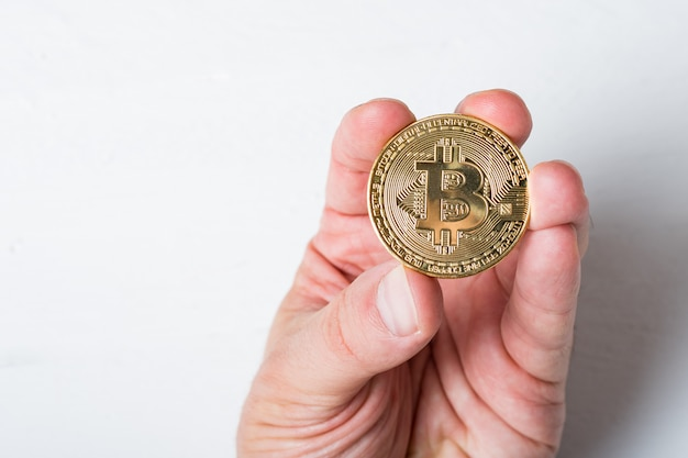 Moeda de bitcoin em uma mão masculina. fechar-se