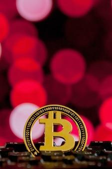 Moeda de bitcoin no teclado do computador em vermelho com luzes desfocadas