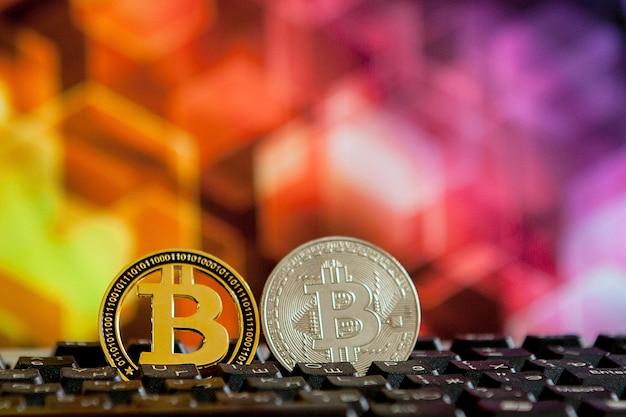 Moeda de bitcoin no teclado do computador na superfície de néon desfocada