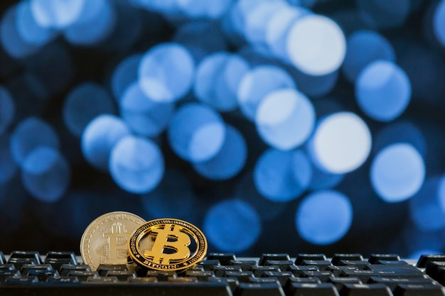 Moeda de bitcoin no teclado do computador no fundo do bokee