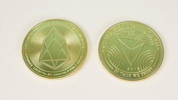 Moeda de criptografia nome eos em fundo branco. moedas de símbolo de criptomoedas físicas douradas.