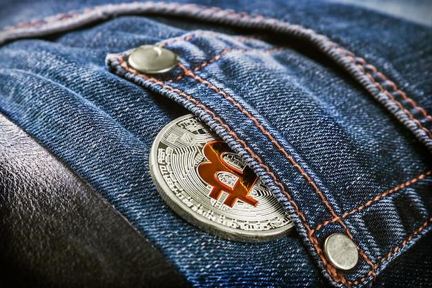 Moeda de criptomoeda bitcoin no bolso da calça jeans
