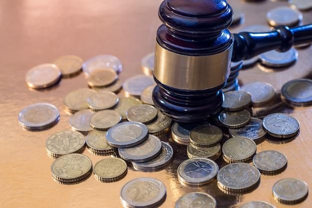 Moeda de euro e martelo isolado em ouro