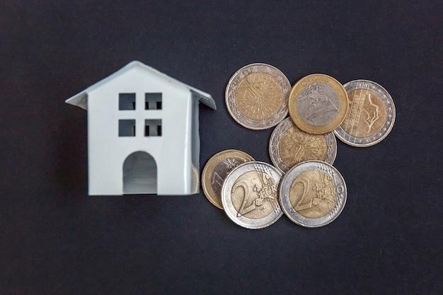 Moeda de euro e pequena casa de brinquedo simbólica