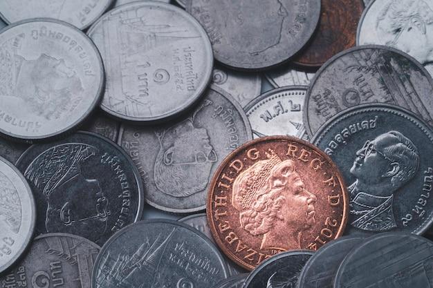 Moeda de libra esterlina de bronze em outro fundo de moedas, economia de câmbio de moeda e conceito de investimento.