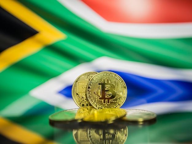 Moeda de ouro bitcoin e bandeira desfocada do fundo da áfrica do sul. conceito de criptomoeda virtual.