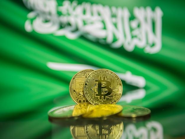 Moeda de ouro bitcoin e bandeira desfocada do fundo da arábia saudita. conceito de criptomoeda virtual.