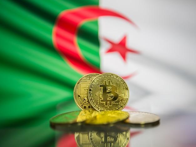 Moeda de ouro bitcoin e bandeira desfocada do fundo da argélia. conceito de criptomoeda virtual.