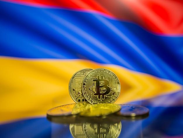 Moeda de ouro bitcoin e bandeira desfocada do fundo da armênia. conceito de criptomoeda virtual.