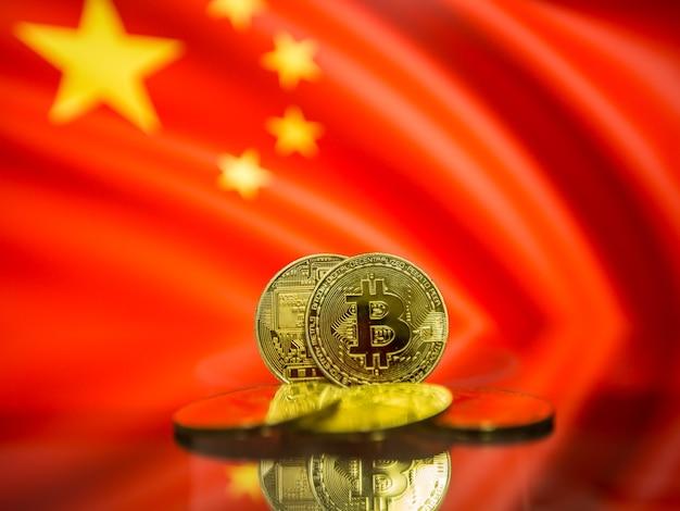 Moeda de ouro bitcoin e bandeira desfocada do fundo da china. conceito de criptomoeda virtual.