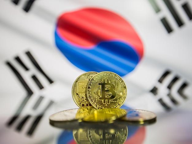 Moeda de ouro bitcoin e bandeira desfocada do fundo da coreia do sul. conceito de criptomoeda virtual.