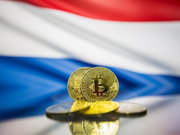 Moeda de ouro bitcoin e bandeira desfocada do fundo da holanda. conceito de criptomoeda virtual.