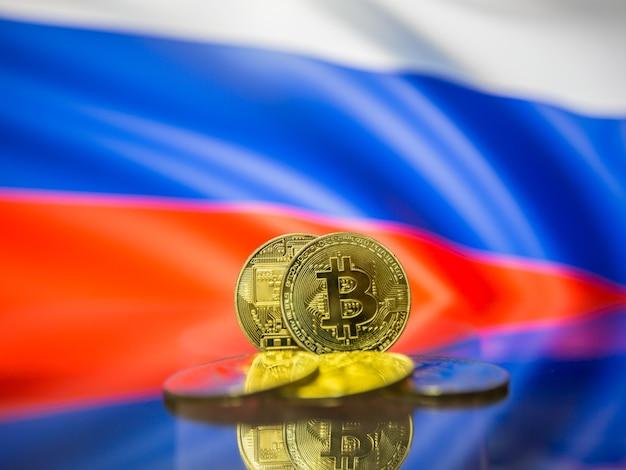 Moeda de ouro bitcoin e bandeira desfocada do fundo da rússia. conceito de criptomoeda virtual.