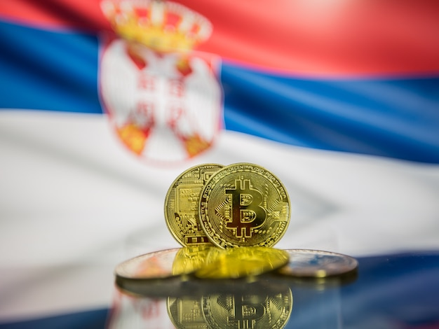 Moeda de ouro bitcoin e bandeira desfocada do fundo da sérvia. conceito de criptomoeda virtual.