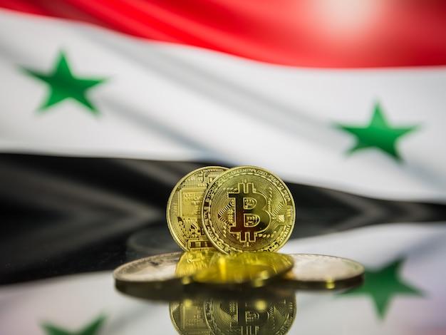 Moeda de ouro bitcoin e bandeira desfocada do fundo da síria. conceito de criptomoeda virtual.