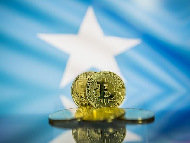 Moeda de ouro bitcoin e bandeira desfocada do fundo da somália. conceito de criptomoeda virtual.