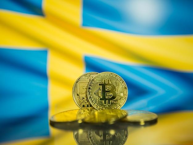 Moeda de ouro bitcoin e bandeira desfocada do fundo da suécia. conceito de criptomoeda virtual.