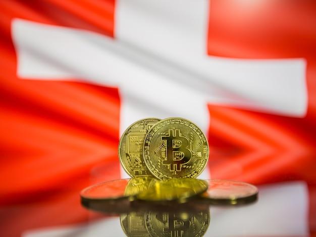 Moeda de ouro bitcoin e bandeira desfocada do fundo da suíça. conceito de criptomoeda virtual.