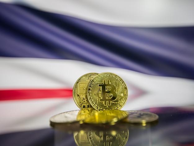 Moeda de ouro bitcoin e bandeira desfocada do fundo da tailândia. conceito de criptomoeda virtual.